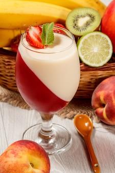 Kers en melkgelei met aardbeistuk in het glas met muntblaadjes, verse aardbeien, nectarine, limoen, kiwi, banaan, appel in een rieten mand op een houten tafel