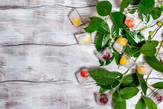 Kers in ijsblokje met tak op wit geschilderde houtstructuur als achtergrond bovenaanzicht