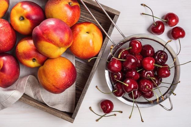 Kers in klein vergiet en nectarines in doos.