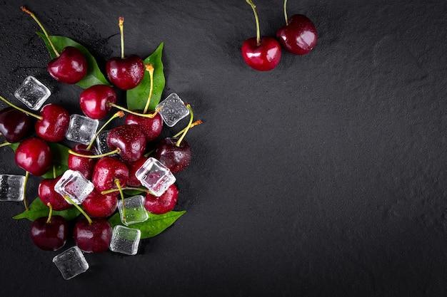 Kers met blad en waterdruppels op zwarte stenen tafel.