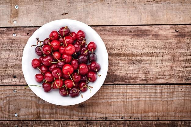 Kers met waterdruppels op witte kom op donkerbruine stenen tafel. verse rijpe kersen. zoete rode kersen. bovenaanzicht. rustieke stijl. fruit achtergrond