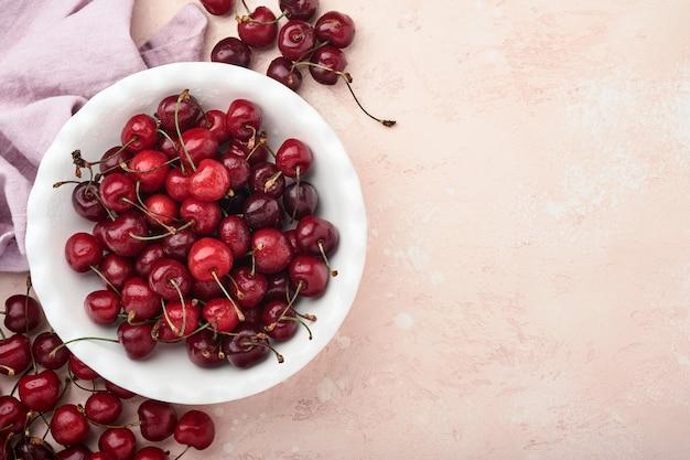 Kers met waterdruppels op witte kom op roze stenen tafel. verse rijpe kersen. zoete rode kersen. bovenaanzicht. rustieke stijl. fruit achtergrond