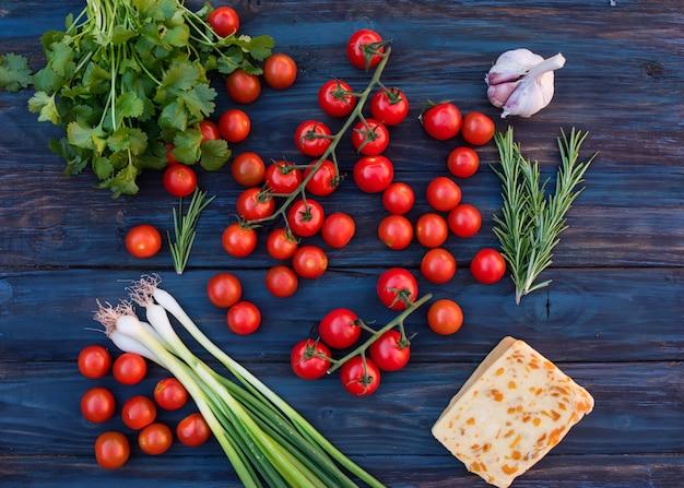 Kersen, groene lente-uitjes, groene rozemarijn, bladeren van koriander, zoete kaas, knoflook op donkere rustieke houten achtergrond