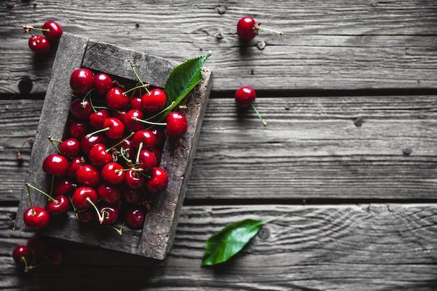 Kersen in een houten krat over een houten achtergrond in een oude houten doos, gezonde voeding, fruit