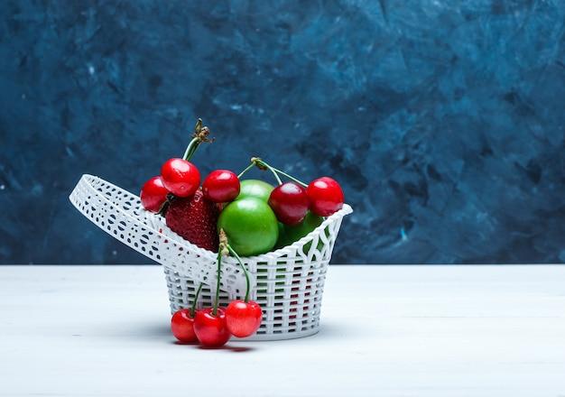 Kersen in een mand met aardbeien en groene pruimen