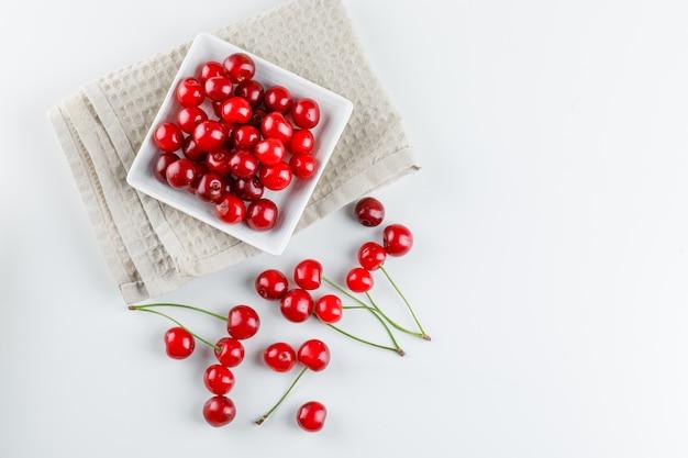 Kersen in een plaat op wit en keukenhanddoek