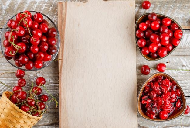Kersen in kommen en mand met jam op houten en snijplank