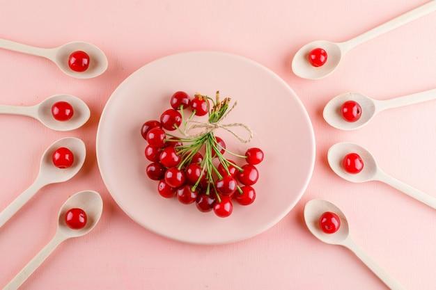 Kersen in plaat en houten lepels op een roze tafel. plat lag.