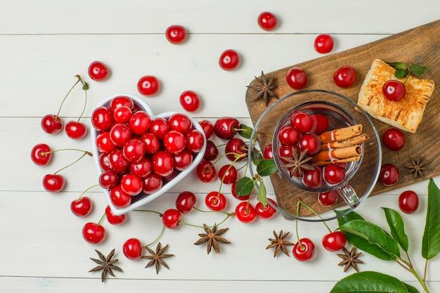 Kersen met gebak, bladeren, kruiden in kom en glas op houten en snijplank.