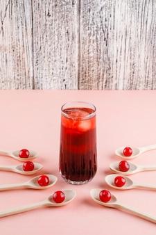 Kersen met ijzige drank in lepels op roze en houten ruimte, zijaanzicht.