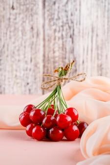 Kersen met textiel zijaanzicht op roze tafel