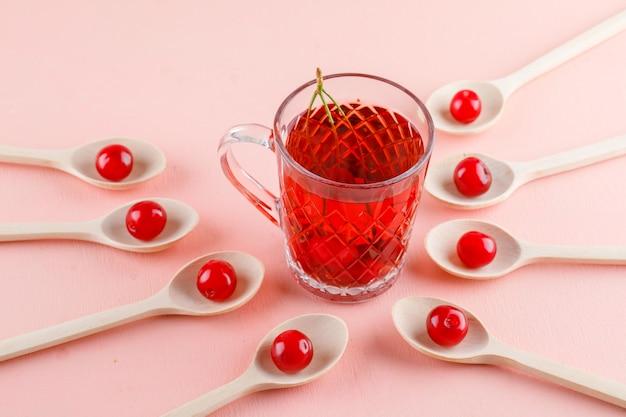 Kersen met thee in houten lepels op roze ruimte, hoge hoekmening.