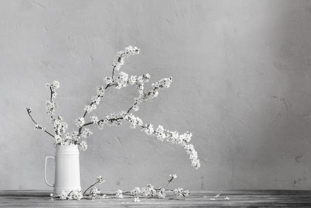 Kersenbloemen in witte kruik op oude houten lijst