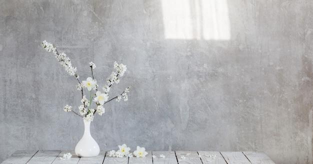 Kersenbloemen in witte vaas op oppervlakte oude grijze muur