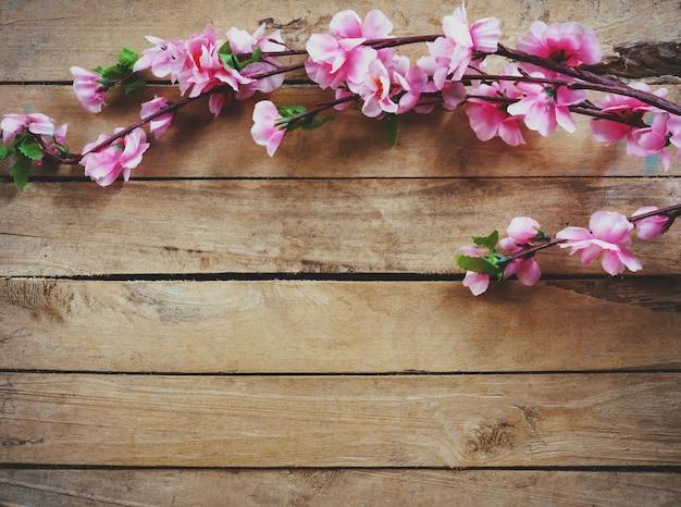 Kersenbloesem en kunstbloemen op vintage houten achtergrond met kopie ruimte.