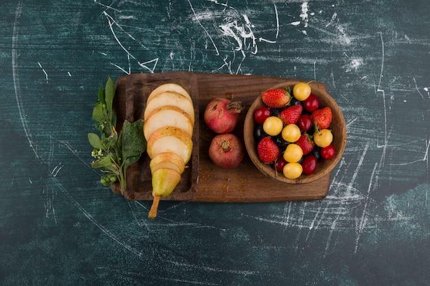 Kersenbordje met granaatappel en peren op een houten schaal in het midden