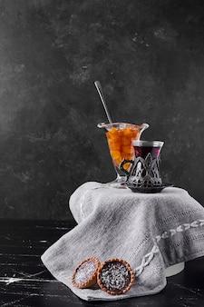 Kersenconfituur met tartalettes en een glas thee.