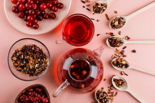 Kersenjam in een kom met gedroogde kruiden, thee, kersen op een roze