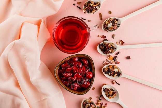 Kersenjam met gedroogde kruiden, thee in een kom op textiel en roze
