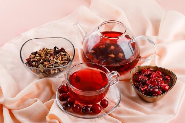 Kersenjam met kersen, thee, gedroogde kruiden in een kom op roze en textiel