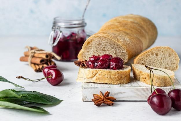 Kersenjam met kruiden (kaneel, anijs) met verse kersen in de potten en brood.