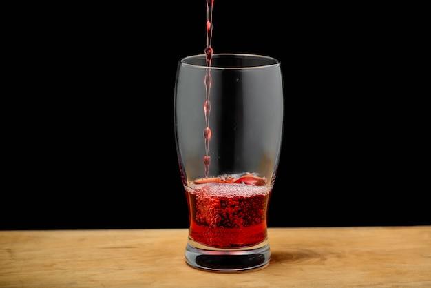 Kersensap het gieten in glas op houten bureau
