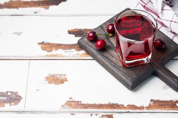 Kersensap in glazen glazen met verse kersenbessen.