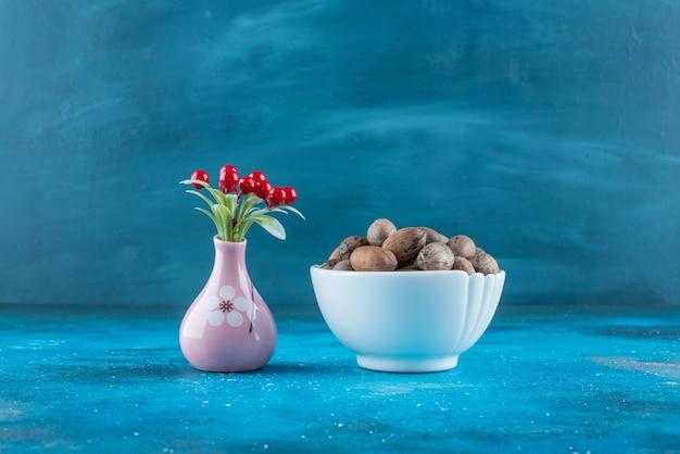 Kersenvruchten in een vaas naast pecannoten in een kom, op de blauwe tafel.