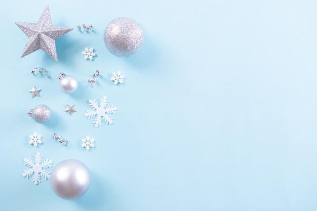 Kerst achtergrond conposition. bovenaanzicht van kerstmisbal met sneeuwvlokken op lichtblauwe pastelkleurachtergrond. kopieer ruimte.