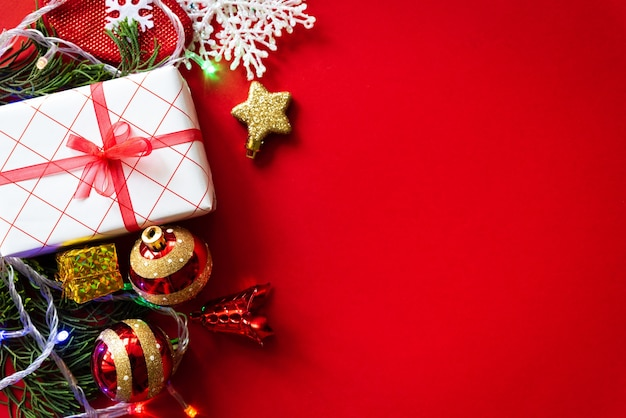 Kerst achtergrond. de doos van de kerstmisgift met rode bal en denneappels op rode achtergrond.