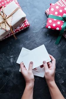 Kerst achtergrond. dozen met geschenken in handen op donker