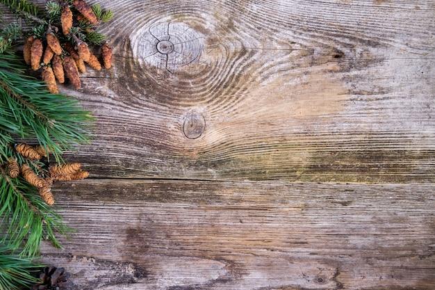 Kerst achtergrond. groene pijnboomtakken met dennenappels op oude houten plank
