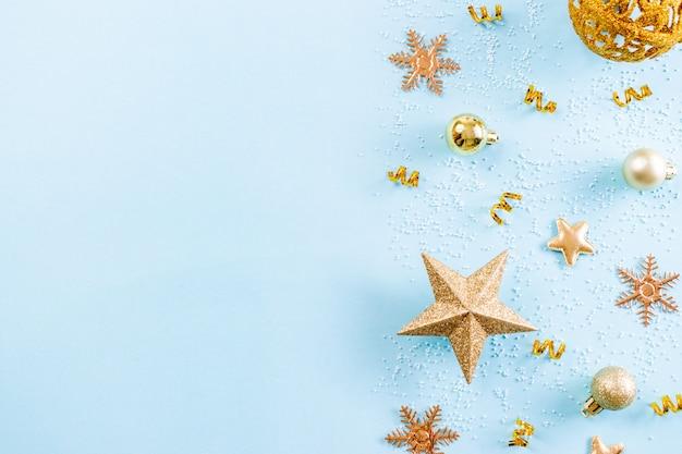 Kerst achtergrond. hoogste mening van gouden decoratie van kerstmis met sneeuwvlokken op lichtblauwe pastelkleurachtergrond. kopieer ruimte.