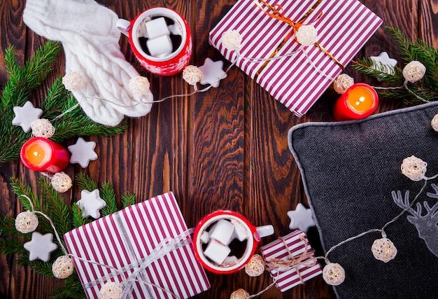 Kerst achtergrond inclusief geschenkdozen, warme chocolademelk, dennentakken en andere decoraties