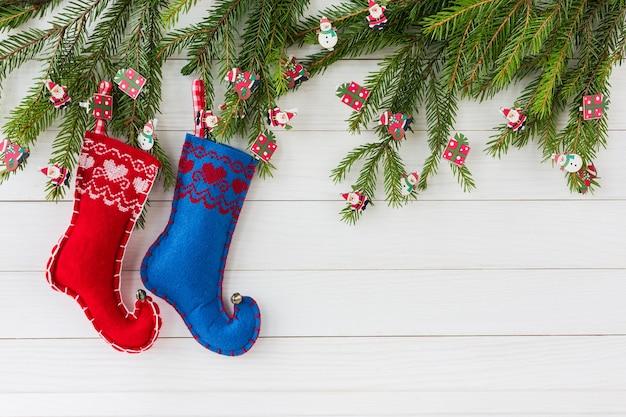 Kerst achtergrond kerst dennenboom met decoratie rode en blauwe kerst sokken op witte houten