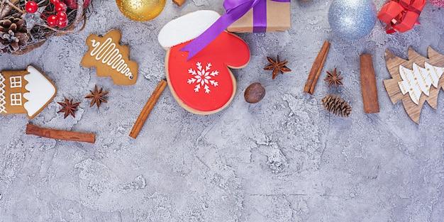 Kerst achtergrond. kerstcadeau, speelgoed, peperkoekkoekjes, kruiden en decoraties op houten tafel. bovenaanzicht