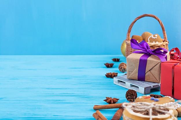 Kerst achtergrond. kerstcadeau, speelgoed, peperkoekkoekjes, kruiden en decoraties op houten tafel