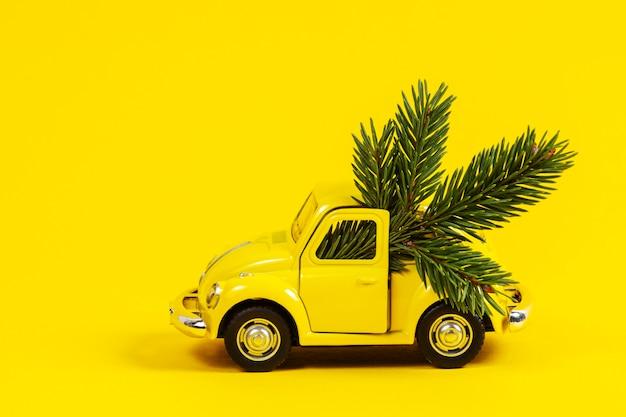 Kerst achtergrond. kleine retro speelgoed modelauto met kerstboomtak op geel