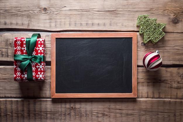 Kerst achtergrond. leisteen bord en kerstboom speelgoed op een houten tafel
