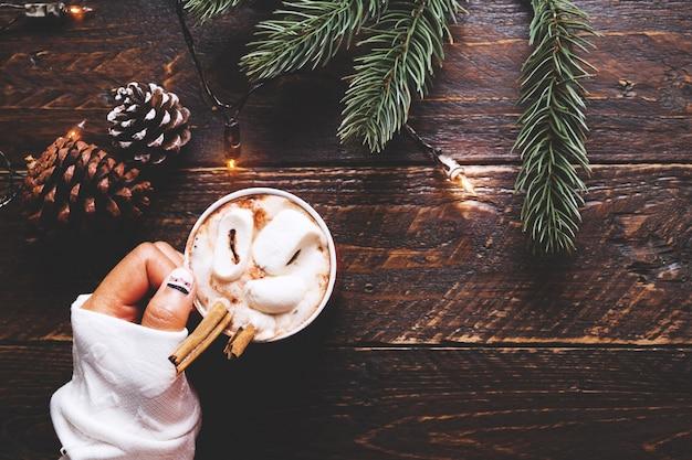 Kerst achtergrond - meisje hand houden kopje warme chocolade op houten tafel met rustieke decoratie en kopieer ruimte, platte lay, bovenaanzicht. vintage kleuren toon stijl.