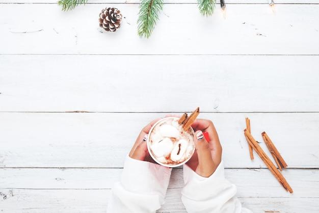 Kerst achtergrond - meisje hand houden kopje warme chocolade op witte tafel met rustieke decoratie en kopie ruimte, platte lay, bovenaanzicht. vintage kleuren toon stijl.