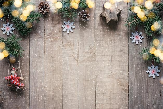 Kerst achtergrond met dennenboom takken kerstverlichting en mini rendier figuur in kerstmuts en...