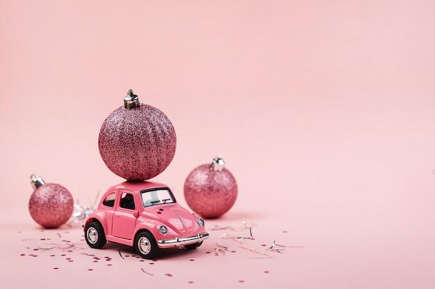 Kerst achtergrond met een roze speelgoedauto op een roze achtergrond. levering concept