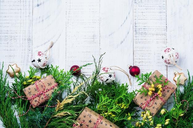 Kerst achtergrond met fir takken, geschenkdoos en kerstballen op houten tafel. selectieve aandacht. bovenaanzicht met kopie ruimte.