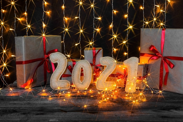 Kerst achtergrond met gehaakte nummers 2021, cadeautjes en lichten