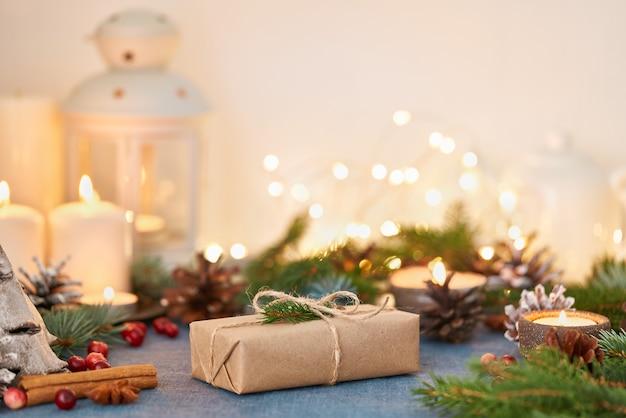 Kerst achtergrond met geschenkdoos en decoraties, kaarsen en lichtslingers. gelukkig nieuwjaar