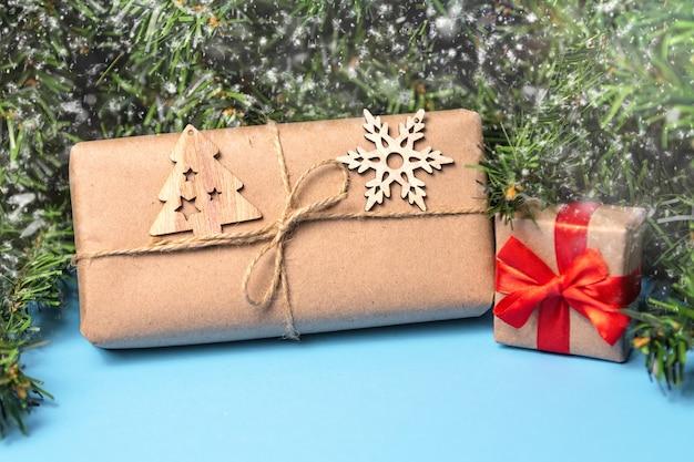 Kerst achtergrond met geschenken in kraft papier en een kerstboom op een blauwe achtergrond. kerst wenskaart. het thema van een wintervakantie. gelukkig nieuwjaar. ruimte voor tekst.