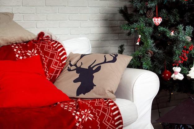 Kerst achtergrond met klassieke nieuwjaarsboom decoratie, rode bank en kussen met hertenprint