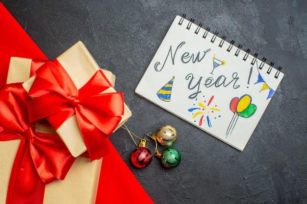 Kerst achtergrond met mooie geschenken met boogvormig lint op een rode handdoek en notitieboekje met nieuwjaarstekeningen op een donkere tafel