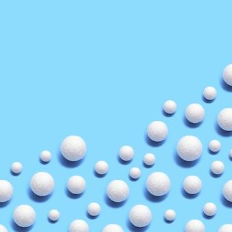 Kerst achtergrond met veel witte sneeuwballen op blauw
